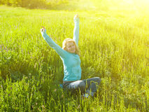 Portrait of young beautiful girl in a green field at sunset. Royalty Free Stock Photo