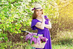 Portrait of young beautiful girl in hat with long hair with flowers in basket on vintage bike. Fashioned woman. Stock Photo