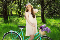 Portrait of young beautiful girl in hat with long hair with flowers in basket on vintage bike. Fashioned woman. Royalty Free Stock Image