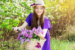 Portrait of young beautiful girl in hat with long hair with flowers in basket on vintage bike. Fashioned woman. Stock Photography