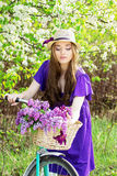 Portrait of young beautiful girl in hat with long hair with flowers in basket on vintage bike. Fashioned woman. Royalty Free Stock Images