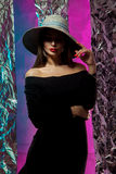 Portrait of young beautiful girl in hat with wide brim. Fashionable portrait of young beautiful girl in hat with wide brim and nice red lips in studio stock photo