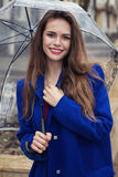 Portrait of young beautiful girl hiding under an umbrella Stock Images