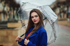 Portrait of young beautiful girl hiding under an umbrella Royalty Free Stock Images