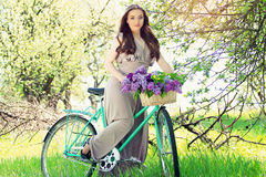 Portrait of young beautiful girl with long hair in bright dress with flowers in basket on vintage bike. Fashioned woman. Stock Image