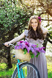 Portrait of young beautiful girl with long hair in bright dress with flowers in basket on vintage bike. Fashioned woman. Attractive girl on an old-fashioned stock images