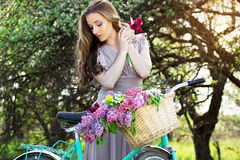 Portrait of young beautiful girl with long hair in bright dress on vintage bike holding flowers. Fashioned woman. Royalty Free Stock Images