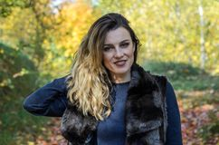 Portrait of a young beautiful girl with long hair in a fur coat during a walk in the autumn park royalty free stock photo