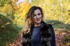 Portrait of a young beautiful girl with long hair in a fur coat during a walk in the autumn park stock image