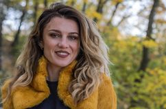 Portrait of a young beautiful girl with long hair in a fur coat during a walk in the autumn park royalty free stock images
