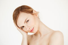 Portrait of young beautiful girl looking at camera touching face over white background. Facial treatment. Beauty Royalty Free Stock Photo