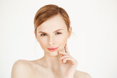 Portrait of young beautiful girl looking at camera touching face over white background. Facial treatment. Beauty Royalty Free Stock Photography