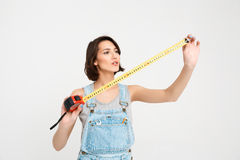 Portrait of young beautiful girl, looking on the tape measure Royalty Free Stock Photo