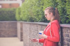 Portrait of young beautiful girl looking at and using smartphone royalty free stock photo