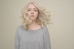 Portrait of a young beautiful girl with luxury hair flying on light background Stock Photography