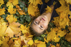 Portrait of young beautiful girl lying on the autumn leaves. Stock Photo