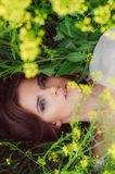 Young beautiful girl in field with yellow flowers stock photo