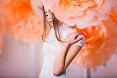 Portrait of young beautiful girl in paper flowers. Young beautiful girl posing in paper flowers in spring studio Stock Photo