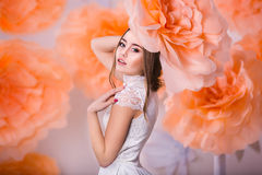 Portrait of young beautiful girl in paper flowers. Young beautiful girl posing in paper flowers in spring studio Royalty Free Stock Photo