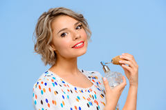 Portrait of young beautiful girl with perfume over blue background. Portrait of young beautiful girl with perfume smiling, looking at camera over blue Stock Photos
