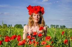 Portrait of a young beautiful girl in a poppy field with a wreath of poppies on her head on a hot summer sunny day Royalty Free Stock Image