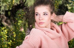 Portrait of young beautiful girl posing in pink sweater. Natural health and beauty. Delicate look Stock Photos