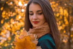 Portrait of a young beautiful girl with red lips that looks down and keeps leaves close-up Royalty Free Stock Image