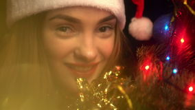 Portrait of young beautiful girl in santa hat looking at thte camera and smiling with christmas tree stock footage