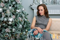 Portrait of young and beautiful girl sitting at sofa during christmas celebration - christmas and new year concept royalty free stock photos