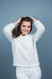 Portrait young beautiful  girl smile and  wearing knitted white  sweater, isolated on grey background.  Royalty Free Stock Photos