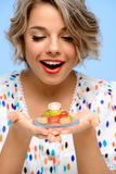Portrait of young beautiful girl with sweets over blue background. Close up portrait of young beautiful girl in white blouse holding candies, smiling over blue Royalty Free Stock Image