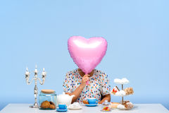 Portrait of young beautiful girl with sweets over blue background. Portrait of young beautiful girl in white blouse sitting at table with sweets, holding pink Royalty Free Stock Photos
