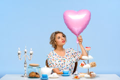 Portrait of young beautiful girl with sweets over blue background. Portrait of young beautiful girl in white blouse sitting at table with sweets, holding pink Royalty Free Stock Images