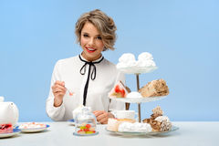 Portrait of young beautiful girl with sweets over blue background. Portrait of young beautiful girl in white blouse sitting at table with sweets, smiling Stock Photography