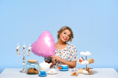 Portrait of young beautiful girl with sweets over blue background. Portrait of young beautiful girl in white blouse sitting at table with sweets, smiling Royalty Free Stock Photo