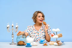 Portrait of young beautiful girl with sweets over blue background. Portrait of young beautiful girl in white blouse sitting at table with sweets, smiling Stock Photo