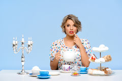 Portrait of young beautiful girl with sweets over blue background. Portrait of young beautiful girl in white blouse sitting at table with sweets, surprised Royalty Free Stock Photography