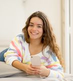 Portrait of young beautiful girl texting and chatting on her smart phone on bed. Happy pretty girl sending messages on mobile phone chatting in social media royalty free stock photography