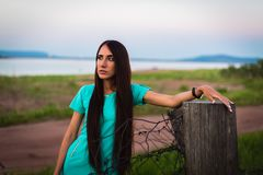 Portrait of young beautiful girl in a turquoise dress near barbed wire in summer outdoor royalty free stock photo