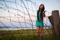 Portrait of young beautiful girl in a turquoise dress near barbed wire in summer outdoor royalty free stock images
