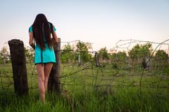 Portrait of young beautiful girl in a turquoise dress near barbed wire in summer outdoor stock photography