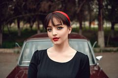 Portrait of a young beautiful girl in vintage clothes next to a retro car.  royalty free stock photography