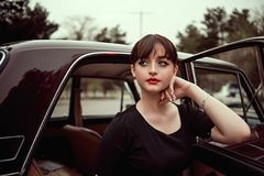 Portrait of a young beautiful girl in vintage clothes next to a retro car.  royalty free stock photo