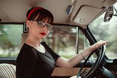 Portrait of a young beautiful girl in a vintage dress in a retro car.  stock photos