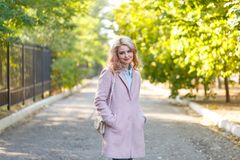 Portrait of a young beautiful girl in a pink coat. In the park. royalty free stock photos