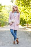 Portrait of a young beautiful girl in a pink coat. In the park. stock image