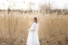 Portrait of young beautiful girl in the white dress in wheat field, walking, carefree. Enjoying the beautiful sunny day stock photos
