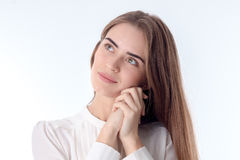 Portrait of a young beautiful girl who folded her hands together and pondered isolated on white background Stock Image