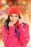 Portrait of young beautiful girl in winter style clothes. The image is taken on a light snowy background Royalty Free Stock Image