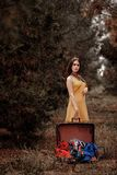 Portrait of a young beautiful girl in a yellow vintage dress with an open vintage suitcase. In her hands from which the clothes spilled out royalty free stock image